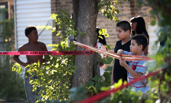 Residents watch as Chicago Police SWAT team members surround a house in the Humboldt Park neighborhood where they believe a man responsible for a nearby murder was hiding on July 27, 2017, in Chicago, Ill. (Scott Olson/Getty Images)