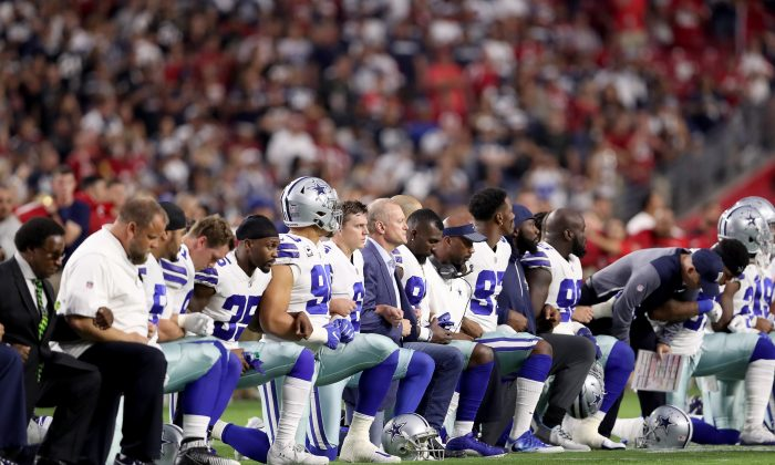 Members of the Dallas Cowboys take a knee before the start of the national anthem at an NFL game against the Arizona Cardinals at the University of Phoenix Stadium in Glendale, Arizona, on Sept. 25, 2017. (Christian Petersen/Getty Images)