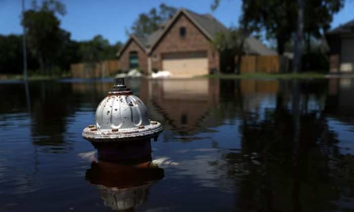 The top of a fire hydrant sticks out of floodwaters in front of a home on in Texas.  (Justin Sullivan/Getty Images)