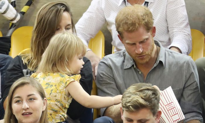 Prince Harry (R) sits with David Henson's wife Hayley Henson (L) and daughter Emily Henson at the Sitting Volleyball Finals during the Invictus Games 2017 at Mattamy Athletic Centre on Sept. 27, 2017, in Toronto. (Chris Jackson/Getty Images for the Invictus Games Foundation)