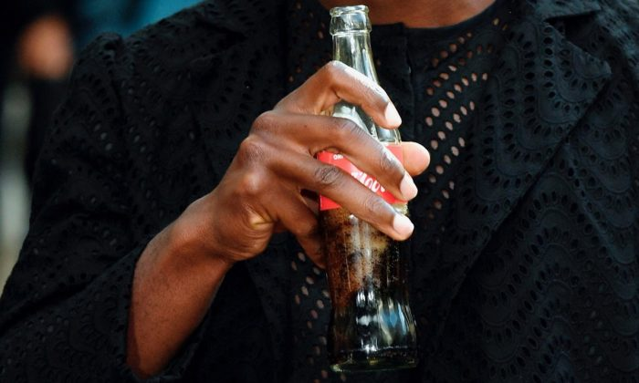 A model drinks a Coca-Cola in Paris, on Sept. 26, 2017. (Bertrand Guay/AFP/Getty Images)