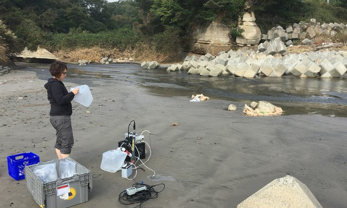 Virginie Sanial, a scientist at Woods Hole Oceanographic Institution, samples groundwater beneath beaches in Japan. Virginie and her team found contaminated sands are releasing radionuclides into the ocean. (Matt Charette/Woods Hole Oceanographic Institution)