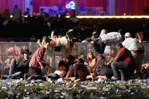 People scramble for shelter at the Route 91 Harvest country music festival after apparent gun fire was heard in Las Vegas on Oct. 1, 2017. (David Becker/Getty Images)