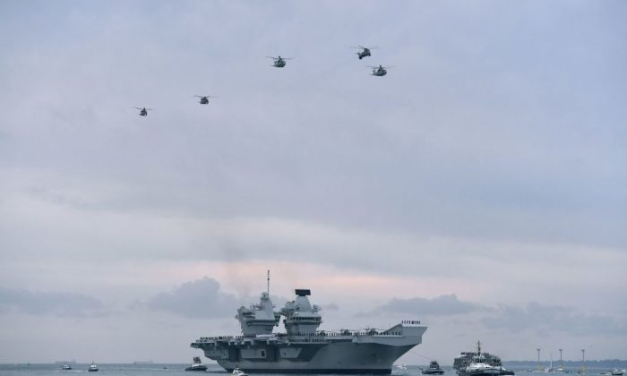 Wildcat and Merlin helicopters fly above the 65,000-tonne British aircraft carrier HMS Queen Elizabeth as tug boats manoeuver it into Portsmouth Harbour in Portsmouth, southern England on Aug. 16, 2017. (Ben Stansall/AFP/Getty Images)
