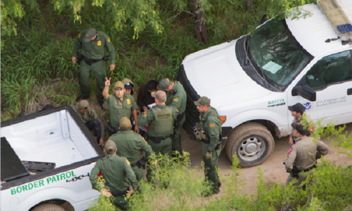 A view from a Customs and Border Protection helicopter, shows Texas Border Patrol agents and Texas State Troopers detaining aliens who were trying to remain hidden after illegally crossing the border from Mexico, near Hidalgo, Texas, on May 30, 2017. (Benjamin Chasteen/The Epoch Times)