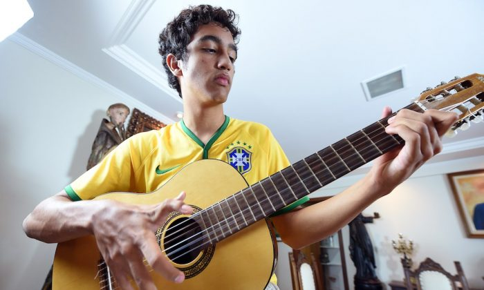 Joao de Assis, who is born with twelve fingers, plays guitar in his home in Brasilia, on June 21, 2014. (AFP PHOTO/ EVARISTA SA)