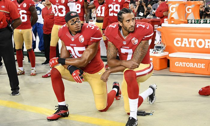 Colin Kaepernick #7 and Eric Reid #35 of the San Francisco 49ers kneel in protest during the national anthem prior to playing the Los Angeles Rams in their NFL game at Levi's Stadium in Santa Clara, California, on Sept. 12, 2016.  (Thearon W. Henderson/Getty Images)