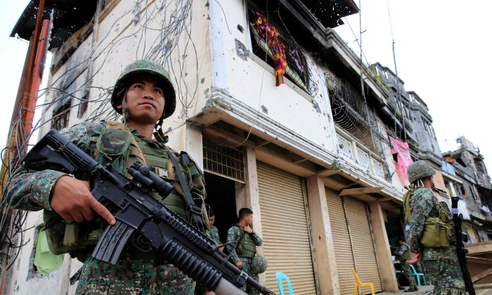 Government soldiers stand guard in front of damaged building and houses in Sultan Omar Dianalan boulevard at Mapandi district in Marawi city, southern Philippines, Sept. 13, 2017. (Reuters/Romeo Ranoco)
