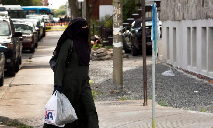 A woman wearing a niqab as she walks in a street in Montreal. Quebec lawmakers have passed a religious neutrality bill that obliges citizens to uncover their faces while giving and receiving state services. (The Canadian Press/Ryan Remiorz)