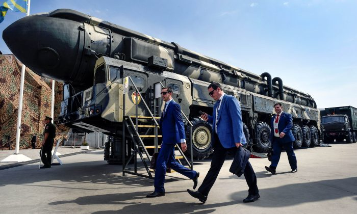 Military specialists walk past a Russian Topol intercontinental ballistic missile (ICBM) at the exposition field in Kubinka Patriot Park outside Moscow on Aug. 22, 2017. (Alexander Nemenov/AFP/Getty Images)