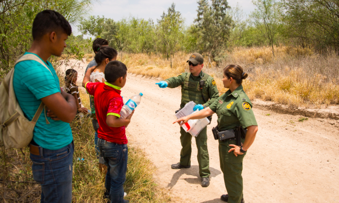 Border Patrol agents process three unaccompanied minors from Honduras (C) while an adult male (L) from Honduras looks on. A man and his son are partially obscured behind them, in Hidalgo County, Texas, on May 26. (Benjamin Chasteen/The Epoch Times)