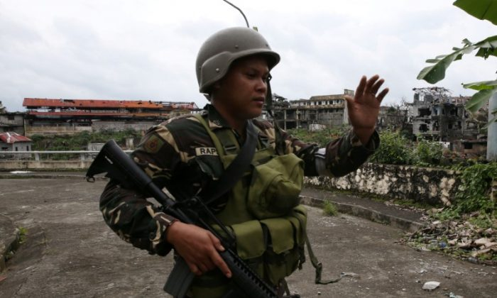 A government soldier gestures during as they clear the area with the local government members inside a war-torn in Marawi city, southern Philippines Oct. 19, 2017. (Reuters/Romeo Ranoco)