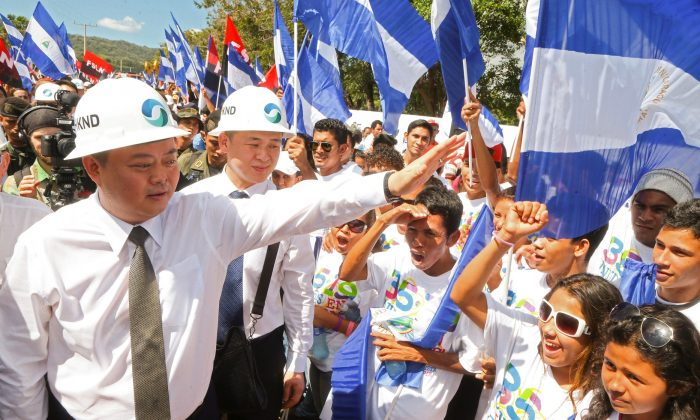 Chinese businessman Wang Jing (L) of HKND Group greets locals during the inauguration of the Nicaragua Canal in Tola, Nicaragua on Dec. 22, 2014. The canal project, with US$50 billion invested by the Chinese, is an ambitious rival to the Panama Canal. (Inti Ocon/AFP/Getty Images)