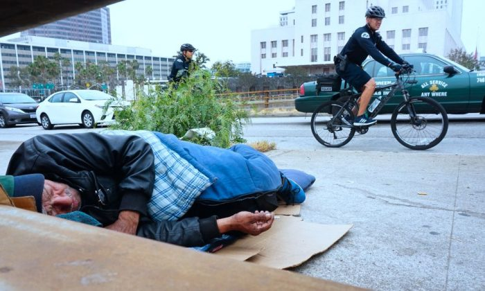 Los Angeles Police Department officers patrol on bicycles past a homeless man on a downtown sidewalk in Los Angeles on June 7, 2017. (FREDERIC J. BROWN/AFP/Getty Images)