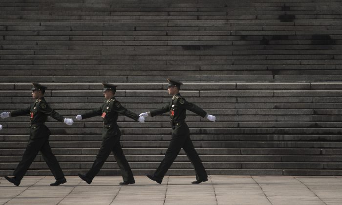 Chinese paramilitary guards walk in front of the Great Hall of the People during the 19th National Congress in Beijing on Oct. 19, 2017. (Fred Dufour/AFP/Getty Images)