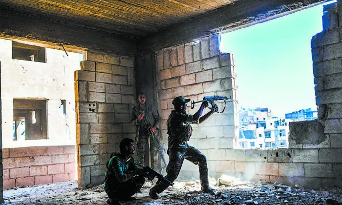 Members of the Syrian Democratic Forces fire their arms during a battle against ISIS terrorists to retake the central hospital of Raqqa, Syria, on the western frontline of the city on Sept. 28. (BULENT KILIC/AFP/GETTY IMAGES)