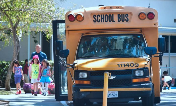 Children walk past a school bus in Monterey Park, Calif., on April 28, 2017. (Frederic J. Brown/AFP/Getty Images)