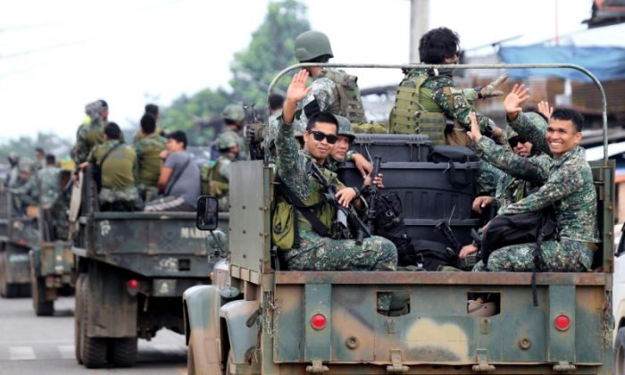 Member of the Philippine Marine Battalion Landing Team (MBLT) wave at residents and motorists while in a military truck as they travel their way back from their five-month combat duty against pro-ISIS terrorist groups, a few days after President Rodrigo Duterte announced the Liberation of Marawi city, southern Philippines on Oct. 21, 2017. (REUTERS/Romeo Ranoco)