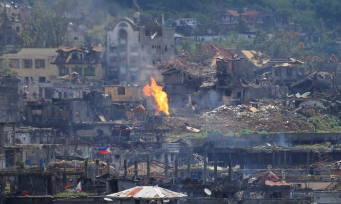 Flame rises as damaged buildings are seen after government troops cleared the area from pro-ISIS terrorists groups inside a war-torn area in Marawi city, southern Philippines Oct. 23, 2017. (Reuters/Romeo Ranoco)