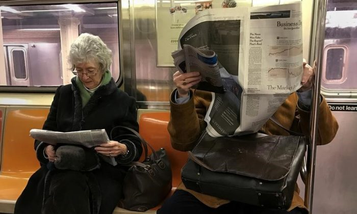 A couple of people ride the subway as they read newspapers as the train pulls into the Times Square stop in Manhattan, New York, on Feb. 17, 2017. (Reuters/Carlo Allegri)