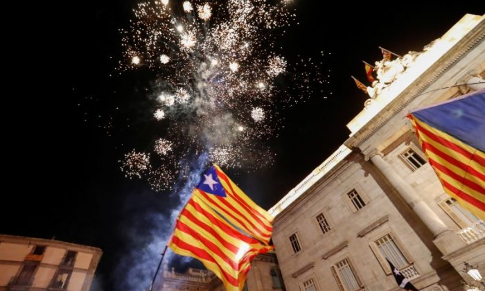 Catalan separatist flags are held up as fireworks go off in Sant Jaume Square in front of the Catalan regional government headquarters during celebrations after the Catalan regional parliament declared independence from Spain in Barcelona. (Reuters/Yves Herman)
