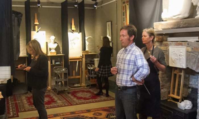 Co-founder and director of The Barnes Atelier of Art, Travis Seymour reviews a student's work in his atelier in London on Sept. 12, 2017. (Milene Fernandez/The Epoch Times)
