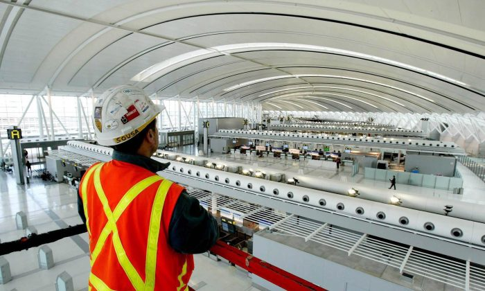 An Aecon employee at the Toronto Pearson International Airport. The Canadian government blocked the takeover of Aecon Group Inc. by a Chinese state-owned company in May 2018 following an extensive national security review. (Canadian Press/AP, Tobin Grimshaw)