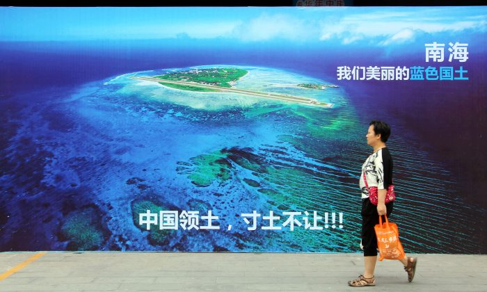 """This photo taken on July 14, 2016 shows a woman walking past a poster of the South China Sea, with the slogan at the bottom """"China's territory, never to yield an inch of our ground"""" on a street in Weifang, Shandong province. China plans to create two Chinese-controlled international maritime courts that would be used to justify its own maritime claims, including those in the South China Sea that have already been ruled unlawful by an international court in July 2016. China may build mobile nuclear power plants in the South China Sea, state media reported on July 15, days after an international tribunal dismissed Beijing's vast claims in the strategically vital waters. (STR/AFP/Getty Images)"""