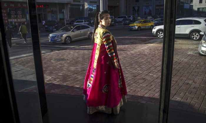 A North Korean restaurant worker tries to attract customers in the border city of Dandong, Liaoning Province, northern China across the Yalu River from the border city of Sinuiju, North Korea on May 23, 2017 in Dandong, China. Many North Korean women who flee are trafficked into forced marriages in China.  (Kevin Frayer/Getty Images)