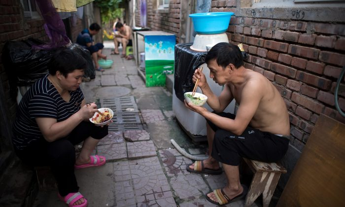 People eat dinner outside their rooms on a street in a migrant village on the outskirts of Beijing on Aug. 17, 2017. (NICOLAS ASFOURI/AFP/Getty Images)