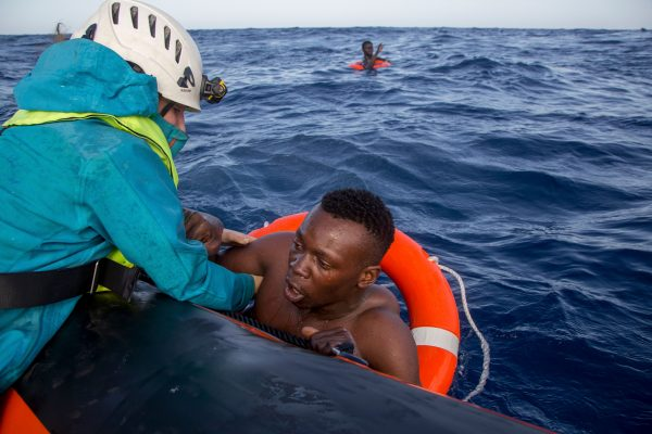 A migrant is helped boarding a boat