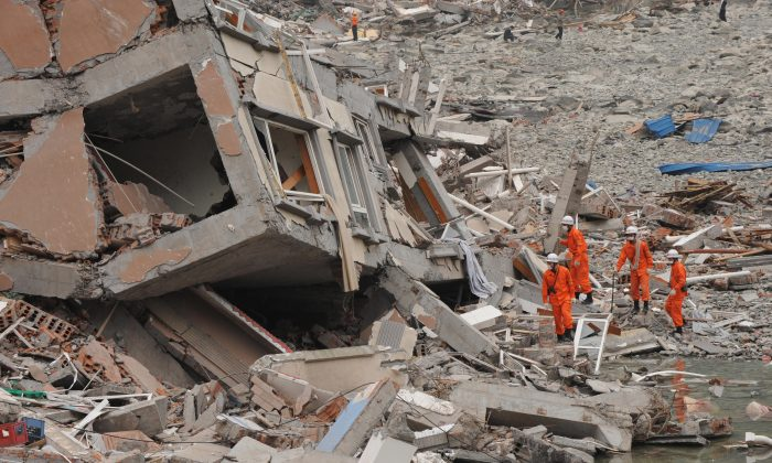 Rescue workers prepare to search a collapsed building at the earthquake damaged town of Beichuan in Sichuan Province on May 17, 2008. (Mark Ralston/AFP/Getty Images)