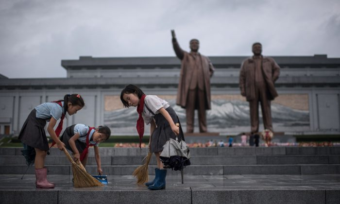 Students clean the steps in front of the statues of late North Korean leaders Kim Il-Sung and Kim Jong-Il in Pyongyang on July 27, 2017. North Korea is censoring messages that can be delivered on Mother's Day, which is used to celebrate mothers who educate their children to be 'good socialist revolutionaries.' (ED JONES/AFP/Getty Images)