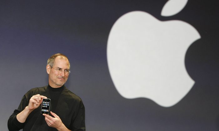 Apple CEO Steve Jobs unveils the first iPhone at the Macworld Conference in San Francisco on Jan. 9, 2007. Steve Jobs and Apple represent the power of producers to shape price and consumer choices. (TONY AVELAR/AFP/Getty Images)
