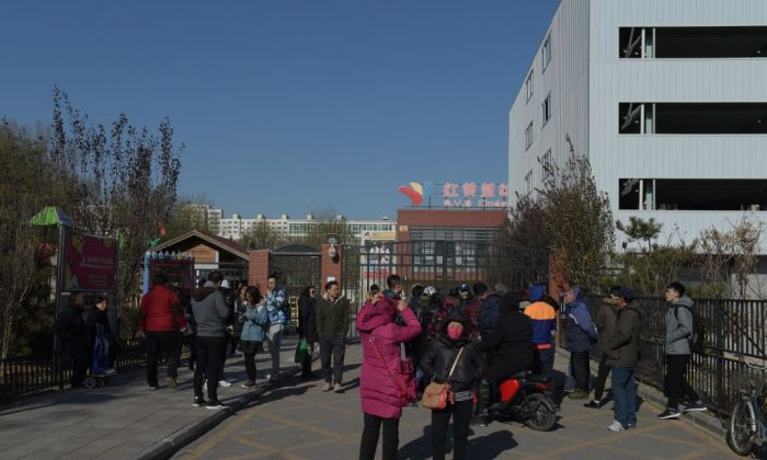 People stand in front of the main gate of the RYB Education kindergarten in Beijing on Nov. 24, 2017. Chinese police have launched an investigation into alleged child abuse at the Beijing kindergarten. (Nicolas Asfouri/AFP/Getty Images)