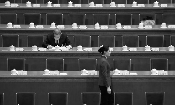 Chinese economist Li Yining sits among empty chairs at the People's Political Consultative Conference held at the Great Hall of the People in Beijing, on March 3, 2013.       (STR/AFP/Getty Images)