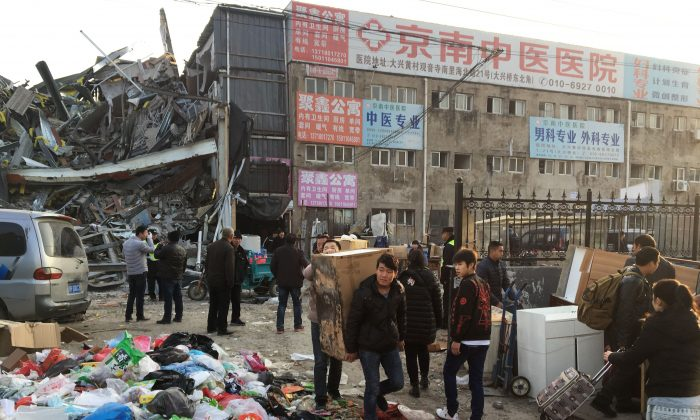 Residents carry their belongings as they evacuate the site of a fatal housing block fire in Beijing on Nov. 19, 2017.  (RYAN MCMORROW/AFP/Getty Images)