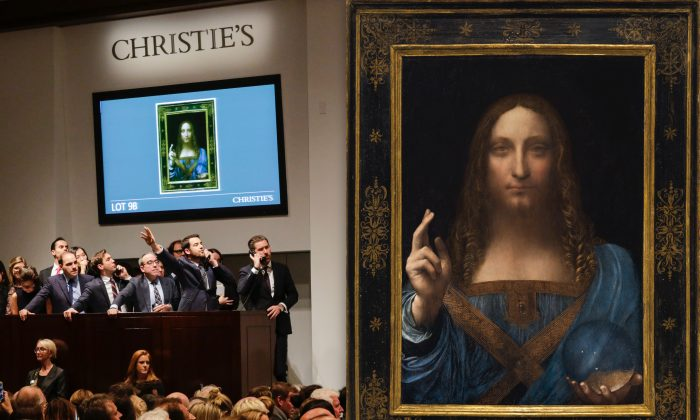 "(L) Agents speak on their phones with their clients while bidding on at the auction of Leonardo da Vinci's ""Salvator Mundi"" during the Post-War and Contemporary Art evening sale at Christie's on Nov. 15, 2017 in New York City. (Eduardo Munoz Alvarez/Getty Images) (R) ""Salvator Mundi,"" circa 1500, by Leonardo da Vinci (1452–1519). Oil on walnut wood panel, 25 7/8 inches by 18 inches, private collection. (Christie's)"