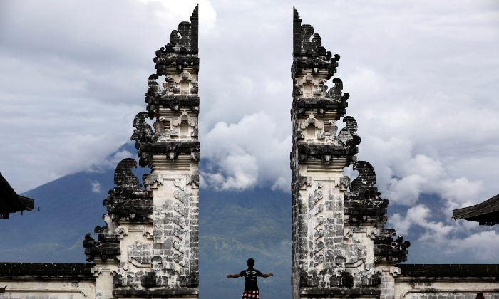 A Balinese man stands at the gate of Lempuyang temple looking towards Mount Agung volcano, in Karangasem Regency, Bali, Indonesia, on Dec. 2, 2017. (Reuters/Darren Whiteside)