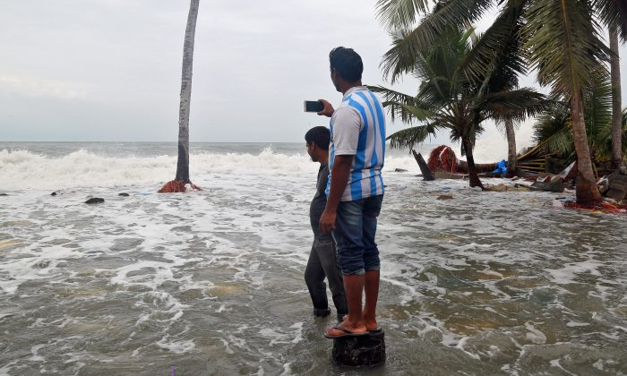 A man uses his mobile phone to take photographs of tides on the shores of the Arabian Sea, after flooding caused by Cyclone Ockhi in the coastal village of Chellanam in the southern state of Kerala, India, December 2, 2017. (Reuters/Sivaram V)