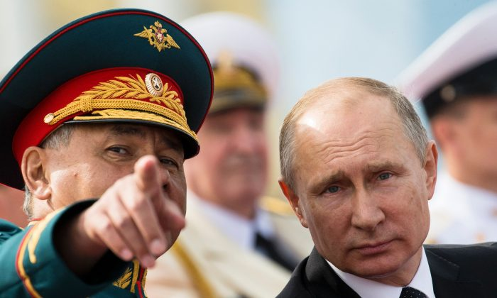 Russian President Vladimir Putin speaks with Defence Minister Sergei Shoigu as they attend a ceremony for Russia's Navy Day in Saint Petersburg on July 30, 2017. Russia has tried to position itself as a key player in the North Korean nuclear crisis. (ALEXANDER ZEMLIANICHENKO/AFP/Getty Images)