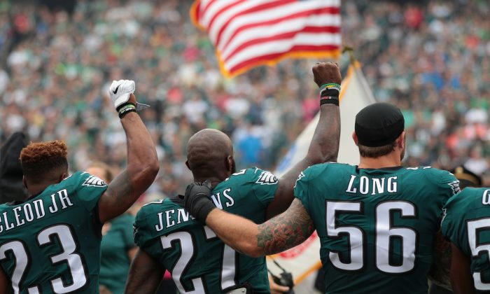 Rodney McLeod #23,  Malcolm Jenkins #27 and  Chris Long #56 of the Philadelphia Eagles stand during the National Anthem during the first quarter at Lincoln Financial Field on October 8, 2017 in Philadelphia, Pennsylvania. The Philadelphia Eagles defeated the Arizona Cardinals 34-7.  (Photo by Rich Schultz/Getty Images)