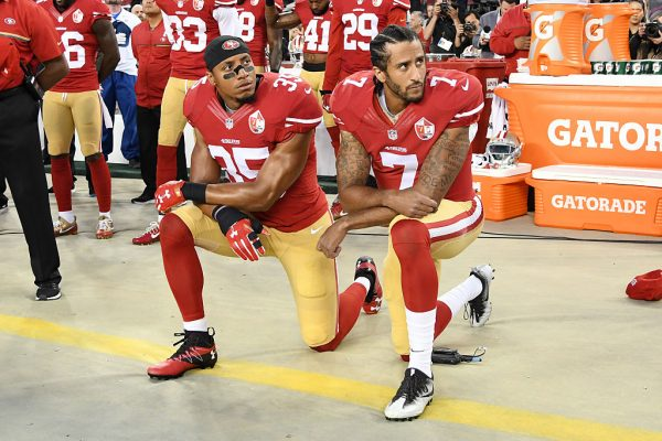 Colin Kaepernick and Eric Reid kneel in protest during the National Anthem in this September 12, 2016 file photo. (Thearon W. Henderson/Getty Images)