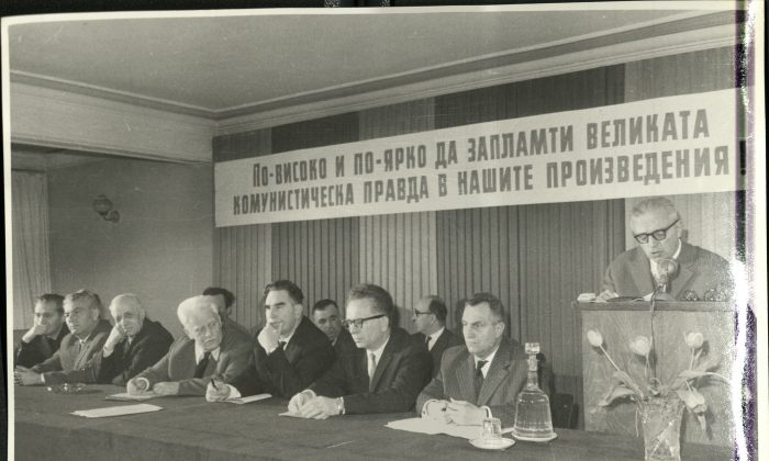 "Dimitar Dimov speaks at a meeting of the Association of Bulgarian Writers in 1964. Among those sitting are Panteley Zarev (second row, second left), Georgi Karaslavov (first row, fifth from left) and Kamen Kalchev (first row, seventh from left), who were some of the most fervent critics of the novel ""Tyutyun."" The slogan above them reads: ""Let the great Communist idea spark ever higher and stronger in our literary works."" (National Museum of Bulgarian Literature)"