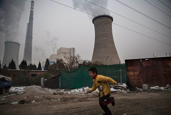 A Chinese boy runs passed a coal fired power plant near his house on the outskirts of Beijing on Nov. 27, 2015. (Kevin Frayer/Getty Images)
