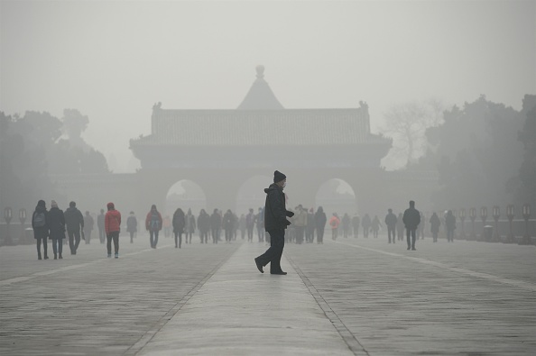 An elderly man walks in front of a group of people during heavy smog in Beijing on Dec. 20, 2016. (Wang Zhao/AFP/Getty Images)
