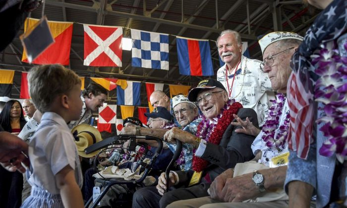 USS Arizona Survivor Don Stratton, seated with his fellow Pearl Harbor Survivors, smiles at a small child at the National Pearl Harbor Remembrance Day during the 75th commemoration, Pearl Harbor, Hawaii, Dec. 7, 2016. The U.S. military co-hosted the event, which provided veterans, family members, service members and the community a chance to honor the sacrifices made by those who were present during the attacks. (U.S. Navy photo / Petty Officer 2nd Class Laurie Dexter)