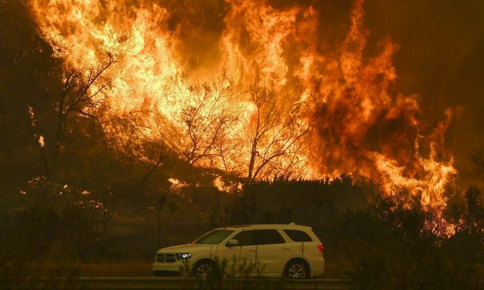 Vehicles pass beside a wall of flames on the 101 highway as it reaches the coast during the Thomas wildfire near Ventura, Calif., on Dec. 6, 2017. (Mark Ralston/AFP/Getty Images)