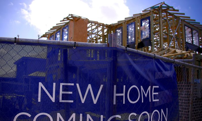 A house under construction can be seen behind an advertising banner at a housing development located in the western Sydney suburb of Oran Park in Australia, Oct. 21, 2017. (Reuters/David Gray/File Photo)