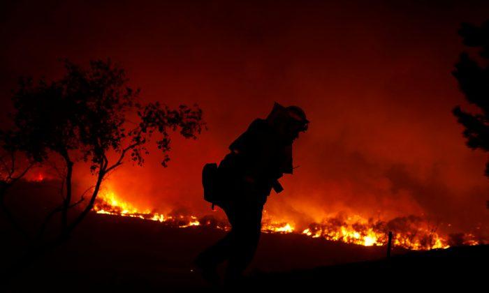 A firefighter is working on extinguishing the Lilac Fire, a fast moving wildfire in Bonsall, California, U.S., December 7, 2017.      (Reuters/Mike Blake)